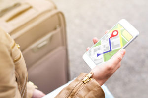 Tourist using map in phone app to navigate and find location of hotel in city