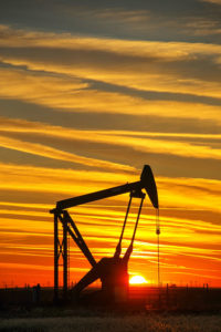 Silhouetted pump jack in the oil field at sunset